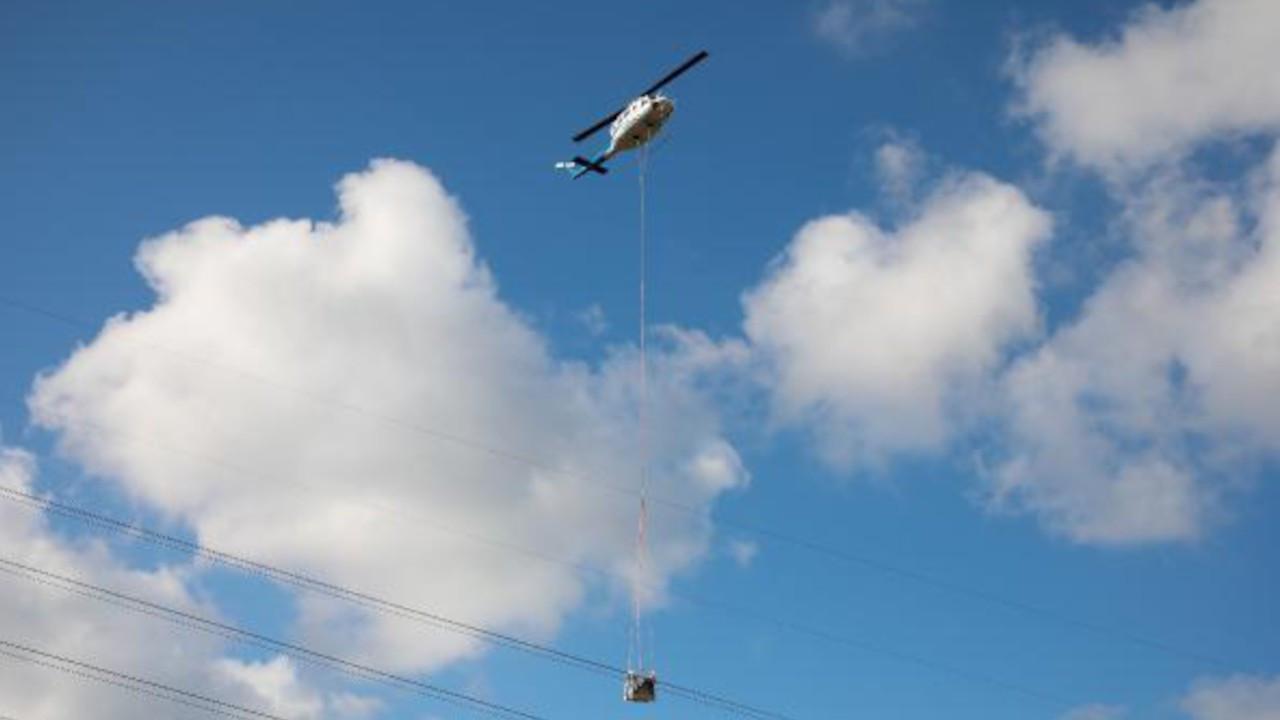Helikopterden sarkıtılarak elektrik hatlarını onarıyorlar